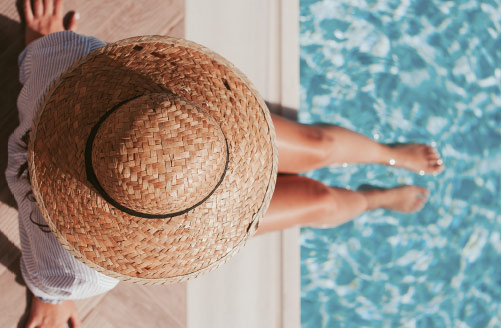 A woman in a sun hat relaxing by a shimering pool