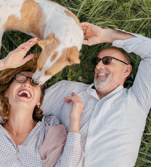 Older couple laying playing with a dog in a field