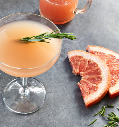 A cocktail glass filled with an orange drink and garnished with a sprig of rosemary surrounded by grapefruit slices, rosemary leaves, and a glass of juice