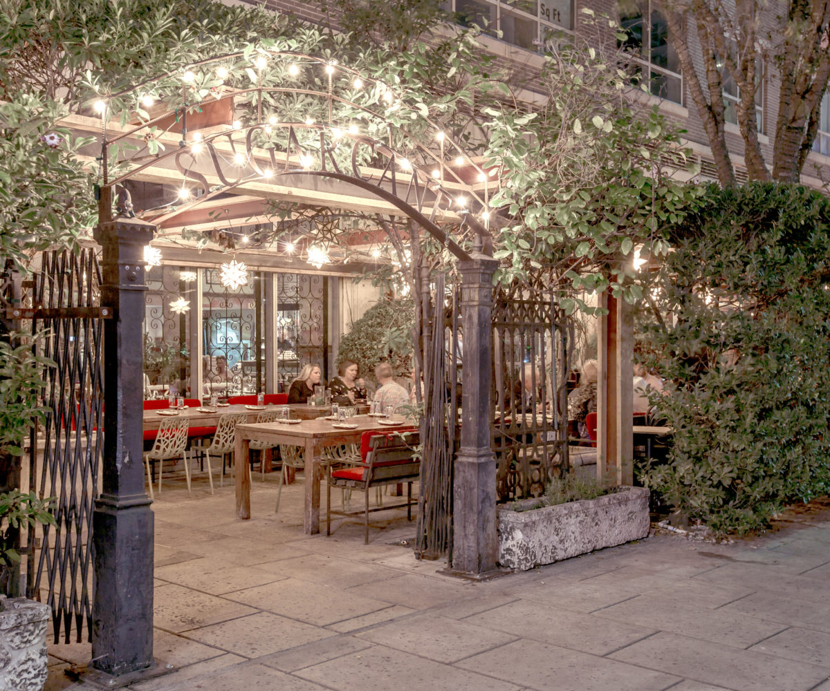 The lush garden patio and twinkling lights of the renowned Sugarcane restaurant in Midtown.